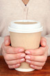Hot drink in paper cup in hands on wooden table close up