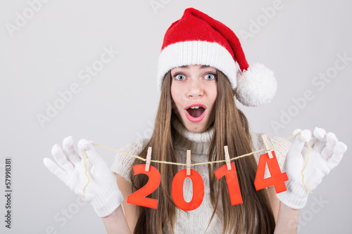 Happy surprised Santa girl holding New Year number decoration