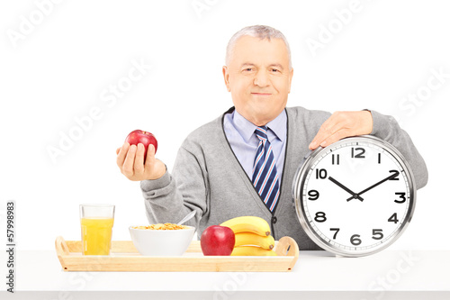 Senior gentleman holding a clock and red apple