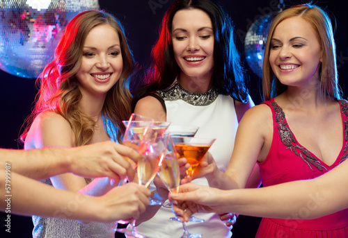 three smiling women with cocktails in club
