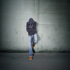 young guy leaning against the wall