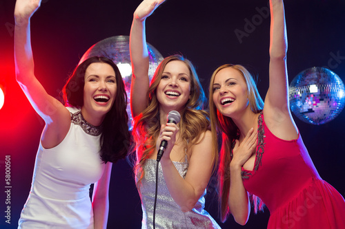 three smiling women dancing and singing karaoke