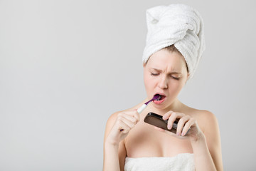 puzzled young girl watching her smart phone while brushing her t