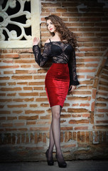Charming young brunette woman in black lace blouse, red skirt
