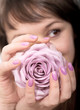 Woman holds lilac-colored rose in manicured hands