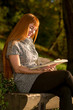 Woman read the book in autumn forest