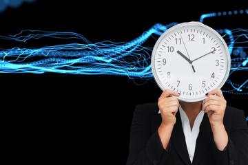 Composite image of businesswoman in suit holding a clock