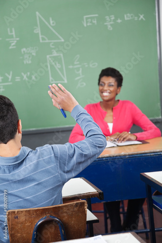 Schoolboy Raising Hand While Teacher Looking At Him