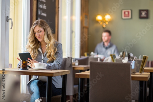 Pregnant Woman Using Digital Tablet At Table