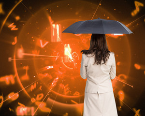 Composite image of rear view of classy businesswoman holding umb