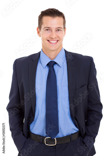 happy businessman posing with hands in pockets