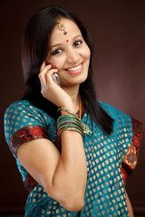 Young traditional woman talking on cellphone