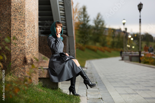 Sad young woman in classic coat sitting at the wall