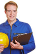 Bauarbeiter lächelt mit Klemmbrett