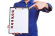Arbeiter im Blaumann zeigt auf Checkliste