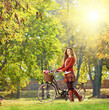 Young female with bicycle relaxing in a park on a sunny day