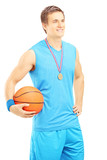 Smiling basketball player with golden medal and basketball