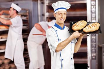 Smiling male baker posing with freshly baked breads in bakery