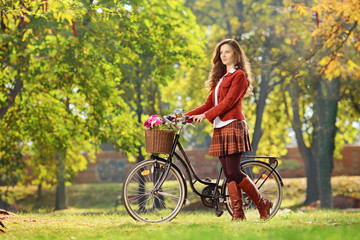 Young female walking with bicycle in park