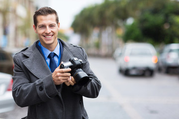 journalist holding a camera in the city