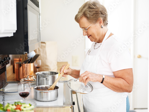 Fotobehang Koken grandmother cooking in the kitchen