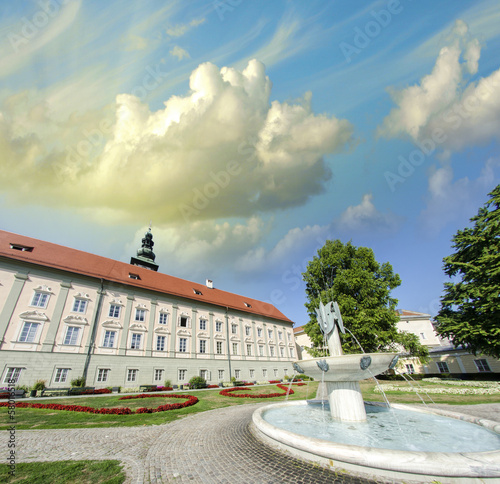 Ancient building in a beautiful city square with fountain and tr