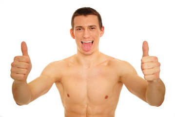 Athletic young man sticks out tongue and shows fingers up