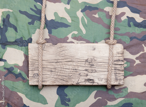 close up of an empty wooden sign hanging on a rope on military f