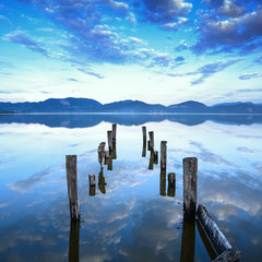 Wooden pier or jetty remains on a lake sunset. Tuscany, Italy © stevanzz