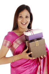 Excited young traditional woman holding gift boxes