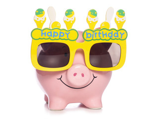 Piggy bank wearing birthday glasses