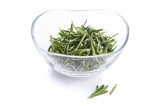 Fresh rosemary leaves in a glass bowl on white background
