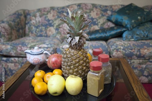 Fresh fruits, spices and teapot on the table ininterior.