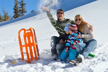 family having fun on fresh snow at winter vacation