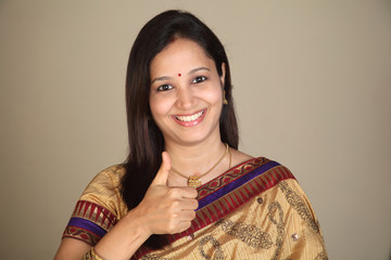 Happy young traditional woman showing thumbs up
