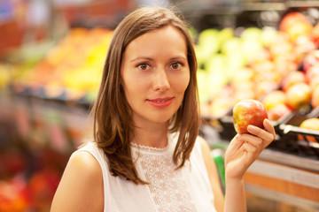 Frau kauft im Obstladen Apfel ein