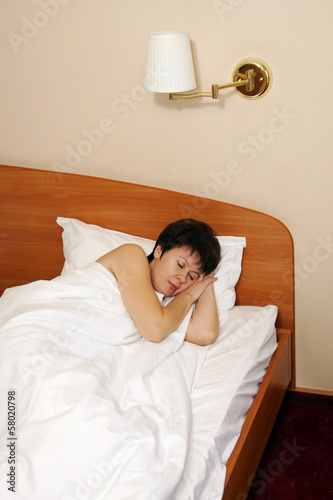 Pretty middle aged woman sleeps in the bed
