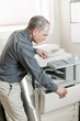 Man opening photocopier in office