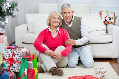 Happy Senior Couple Sitting By Christmas Presents