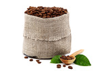 Coffee beans in a canvas bag, wooden spoon and green leaves.