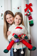 Mother With Daughter Holding Santa Toy At Home