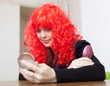Woman in red wig stares into mirror