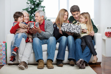 Family With Christmas Presents Sitting In House