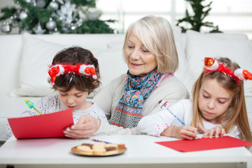 Senior Woman With Siblings Writing Letters To Santa Claus