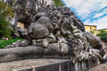 Lion sculpture in Covadonga with the hermitage of the holy cave
