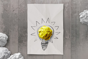 drawing light bulb on crumpled paper with workplace  as creative