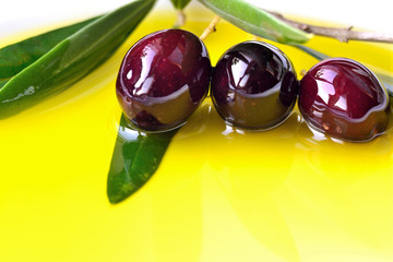 Olive oil  background with black olives closeup