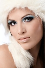 Beauty portrait of woman in fur cap and makeup