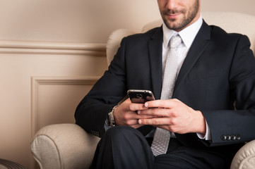 Young businessman sending message with mobile phone sit on armch