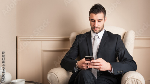 Young businessman using mobile phone sit on armchair.